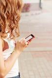 Το όμορφο κορίτσι με τη σγουρή τρίχα που στέκεται στην οδό στο τηλέφωνο υπό εξέταση, στέλνει ένα μήνυμα SMS διαβάζει Στοκ Φωτογραφίες