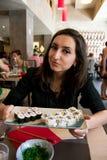 Το όμορφο κορίτσι με τη σκοτεινή τρίχα, που ντύνεται στο Μαύρο κρατά ένα σύνολο πιάτων των σουσιών Στοκ Εικόνα