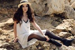 Το όμορφο κορίτσι με τη σκοτεινή τρίχα φορά τα περιστασιακά κομψά ενδύματα και το καπέλο Στοκ εικόνες με δικαίωμα ελεύθερης χρήσης