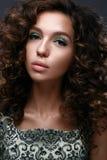 Το όμορφο κορίτσι με τις μπούκλες και πράσινος ακτινοβολεί στα βλέφαρα Η πρότυπη γυναίκα με όμορφο κάνει το επάνω και σγουρό hair στοκ φωτογραφία