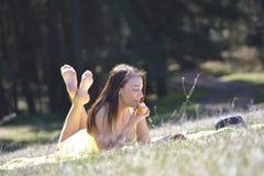 Το όμορφο κορίτσι με το βιβλίο σταθμεύει την άνοιξη Στοκ Φωτογραφία