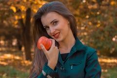 Το όμορφο κορίτσι με το κόκκινο κραγιόν κρατά τη Apple στο χέρι του και χαμογελά την κινηματογράφηση σε πρώτο πλάνο Στοκ Εικόνες