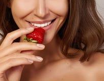 Το όμορφο κορίτσι με το τέλειο χαμόγελο τρώει τα κόκκινα άσπρα δόντια φραουλών και τα υγιή τρόφιμα Στοκ Εικόνες