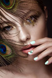 Το όμορφο κορίτσι με το φωτεινό makeup, σχέδιο μανικιούρ και peacock επενδύει με φτερά στο πρόσωπό της Καρφιά τέχνης Στοκ Εικόνα