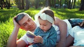 Το όμορφο κορίτσι μικρών παιδιών κάθεται κοντά στους γονείς στην πράσινη χλόη και εξετάζει το σανδάλι της απόθεμα βίντεο
