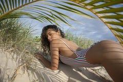 Το όμορφο κορίτσι μπικινιών εναπόκειται στην άκρη της υψηλή Στοκ εικόνες με δικαίωμα ελεύθερης χρήσης