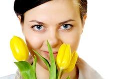 το όμορφο κορίτσι μυρίζει τις τουλίπες κίτρινες Στοκ Εικόνες