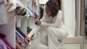 Το όμορφο κορίτσι ο αγοραστής επιλέγει το ύφασμα στο κατώτατο ράφι στο κατάστημα Ποικιλία των χρωματισμένων υφασμάτων Πλάγια όψη φιλμ μικρού μήκους