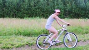 Το όμορφο κορίτσι οδηγά το ποδήλατο στο θερινό πράσινο δάσος στην πορεία απόθεμα βίντεο