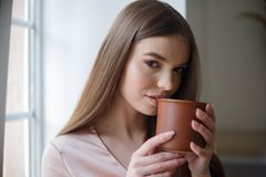 Το όμορφο κορίτσι πίνει τον καφέ και χαμογελά καθμένος στον καφέ στοκ εικόνες