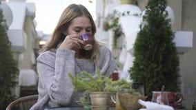 Το όμορφο κορίτσι πίνει τον καφέ στο πεζούλι σε έναν καφέ φιλμ μικρού μήκους