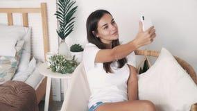 Το όμορφο κορίτσι παίρνει selfie ή το βίντεο στο τηλέφωνο, στέλνει το φιλί αέρα, σε αργή κίνηση απόθεμα βίντεο