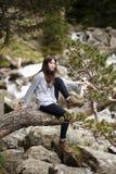 Το όμορφο κορίτσι παραμένει πάνω από ένα βουνό και εξετάζει τον ορίζοντα με ένα όμορφο υπόβαθρο Μια ζωηρόχρωμη φωτογραφία του α Στοκ Φωτογραφία