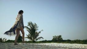 Το όμορφο κορίτσι περπατά κατά μήκος της παραλίας σε ένα pareo απόθεμα βίντεο
