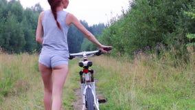 Το όμορφο κορίτσι πηγαίνει με το ποδήλατο στην πορεία κοντά στο δάσος στο θερινό βράδυ, πίσω άποψη απόθεμα βίντεο