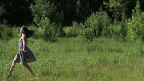 Το όμορφο κορίτσι πηδά χαριτωμένα στη χλόη απόθεμα βίντεο