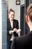 Το όμορφο κορίτσι που ελέγχει την επιχείρησή της κοιτάζει, ρυθμίζοντας τη μανσέτα πριν από τον καθρέφτη Στοκ φωτογραφία με δικαίωμα ελεύθερης χρήσης