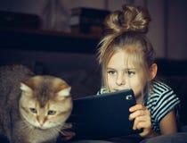 Το όμορφο κορίτσι που κρατά μια ταμπλέτα και εξετάζει τη γάτα Στοκ Εικόνα