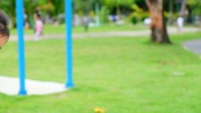 Το όμορφο κορίτσι που παίζει την ταλάντευση χαμογελά ευτυχώς στην παιδική χαρά το θερινό βράδυ απόθεμα βίντεο
