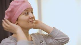 Το όμορφο κορίτσι προσπαθεί beret στο ροζ φιλμ μικρού μήκους
