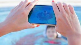 Το όμορφο κορίτσι πυροβολεί το βίντεο στη συσκευή ένα μικρό κορίτσι στη λίμνη απόθεμα βίντεο