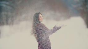 Το όμορφο κορίτσι ρίχνει το χιόνι απόθεμα βίντεο