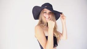 Το όμορφο κορίτσι σε ένα καπέλο με μια μόδα χείλων θέτει φιλμ μικρού μήκους