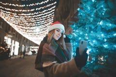 Το όμορφο κορίτσι σε ένα καπέλο Χριστουγέννων στέκεται τη νύχτα σε μια οδό κοντά σε ένα χριστουγεννιάτικο δέντρο και παίρνει self στοκ φωτογραφίες