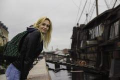 Το όμορφο κορίτσι σε ένα σακάκι εξετάζει τη κάμερα που κλίνει στο κιγκλίδωμα Στοκ Εικόνα