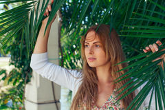 Το όμορφο κορίτσι σε διακοπές με το φοίνικα βγάζει φύλλα Στοκ εικόνες με δικαίωμα ελεύθερης χρήσης