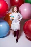 Το όμορφο κορίτσι σε μια άσπρη μπλούζα με ένα μαλακό παιχνίδι έρχεται στη κάμερα Στοκ φωτογραφία με δικαίωμα ελεύθερης χρήσης