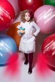 Το όμορφο κορίτσι σε μια άσπρη μπλούζα με ένα μαλακό παιχνίδι έρχεται στη κάμερα Στοκ Φωτογραφία
