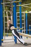 Το όμορφο κορίτσι σε μια φόρμα γυμναστικής στην παιδική χαρά εξετάζει τα δαχτυλίδια Στοκ Φωτογραφία