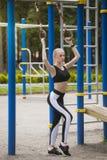 Το όμορφο κορίτσι σε μια φόρμα γυμναστικής στην παιδική χαρά εξετάζει τα δαχτυλίδια Στοκ εικόνες με δικαίωμα ελεύθερης χρήσης