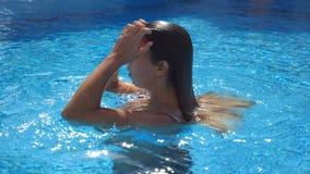 Το όμορφο κορίτσι σκάει επάνω κάτω από το νερό στη λίμνη Η νέα γυναίκα προκύπτει από κάτω από το νερό στη λεκάνη του ξενοδοχείου  φιλμ μικρού μήκους