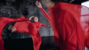 Το όμορφο κορίτσι στα κόκκινα κοστούμια που κάνουν έναν χορό παρουσιάζει εσωτερικό φιλμ μικρού μήκους