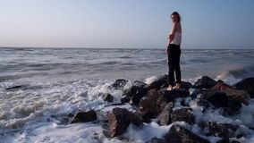 Το όμορφο κορίτσι στην μπλούζα στέκεται στους βράχους στη θάλασσα, γύρω από τα κύματα, ράντισμα φιλμ μικρού μήκους