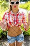 Το όμορφο κορίτσι στην οδό, γυαλιά ηλίου στο φωτεινό πουκάμισο, σορτς τζιν, που στέκεται στον καθαρό φράκτη, διαμορφώνει τον τρόπ Στοκ φωτογραφία με δικαίωμα ελεύθερης χρήσης