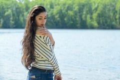 Το όμορφο κορίτσι στην παραλία εξετάζει το νερό Στοκ Εικόνες