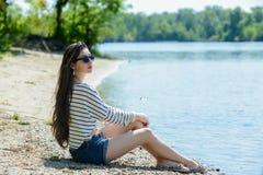 Το όμορφο κορίτσι στην παραλία εξετάζει το νερό Στοκ φωτογραφίες με δικαίωμα ελεύθερης χρήσης