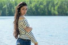 Το όμορφο κορίτσι στην παραλία εξετάζει το νερό Στοκ φωτογραφία με δικαίωμα ελεύθερης χρήσης