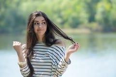 Το όμορφο κορίτσι στην παραλία εξετάζει το νερό Στοκ Φωτογραφίες