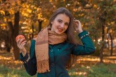 Το όμορφο κορίτσι στις μακριές στάσεις μαντίλι παροξυσμού στο πάρκο κρατά τη Apple και αύξησε ένα χέρι στο κεφάλι της Στοκ Φωτογραφία