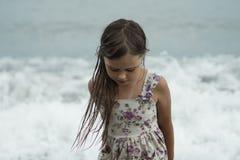 Το όμορφο κορίτσι στο θερινό φόρεμα με την υγρή τρίχα υπερασπίζεται σκεπτικά τη θάλασσα στοκ φωτογραφία