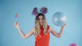 Το όμορφο κορίτσι στο καπέλο κομμάτων χορεύει κάτω από το μειωμένα κομφετί και τα μπαλόνια σε ένα μπλε υπόβαθρο απόθεμα βίντεο