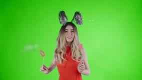 Το όμορφο κορίτσι στο καπέλο κομμάτων χορεύει κάτω από τη μειωμένη φυσαλίδα σαπουνιών σε μια πράσινη οθόνη απόθεμα βίντεο