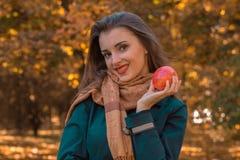 Το όμορφο κορίτσι στο καφετί μαντίλι παροξυσμού κρατά τη Apple και μια κινηματογράφηση σε πρώτο πλάνο χαμόγελου Στοκ φωτογραφία με δικαίωμα ελεύθερης χρήσης