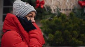 Το όμορφο κορίτσι στο κόκκινο σακάκι μιλά στο smartphone στεμένος στην οδό σε μια φωτεινή χειμερινή ημέρα φιλμ μικρού μήκους