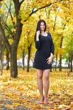 Το όμορφο κορίτσι στο μαύρο φόρεμα και τα κόκκινα παπούτσια στην κίτρινη πόλη σταθμεύουν, πέφτουν εποχή Στοκ Εικόνες