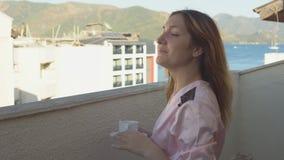 Το όμορφο κορίτσι στο μπουρνούζι πηγαίνει στο μπαλκόνι του δωματίου της στο ξενοδοχείο και απολαμβάνει τον καφέ απόθεμα βίντεο